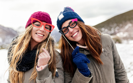 Two young women with fake glasses having fun in the snowy mountains