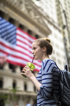 USA, New York City, woman drinking a smoothie in front of New York Stock Exchange LANG_EVOIMAGES