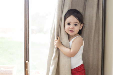 Portrait of a toddler girl playing peek-a-boo behind the curtain LANG_EVOIMAGES