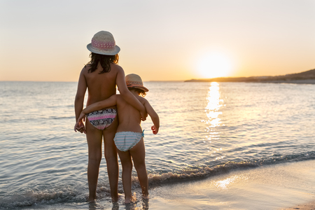 Spain, Menorca, two girls watching the sunset on the beach LANG_EVOIMAGES