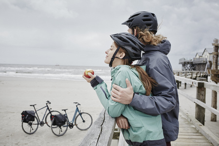 Germany, Schleswig-Holstein, St Peter-Ording, couple on a bicycle trip having a break on jetty at the beach LANG_EVOIMAGES