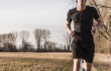 Man running in rural landscape LANG_EVOIMAGES