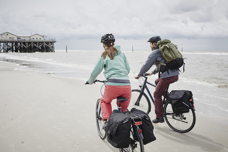 Germany, Schleswig-Holstein, St Peter-Ording, couple riding bicycle on the beach LANG_EVOIMAGES