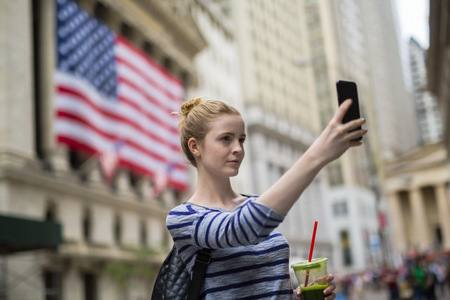 USA, New York City, woman taking selfie in front of New York Stock Exchange LANG_EVOIMAGES