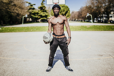 Portrait of barechested basketball player on court LANG_EVOIMAGES