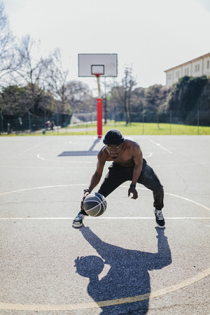 Barechested basketball player in action on court