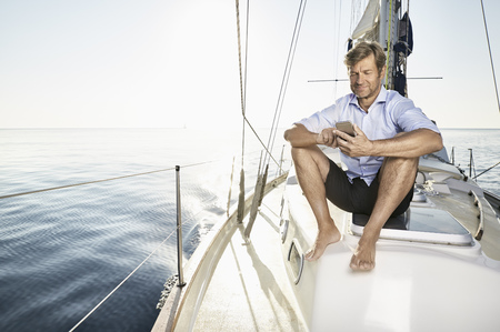 Smiling mature man sitting on his sailing boat using cell phone LANG_EVOIMAGES
