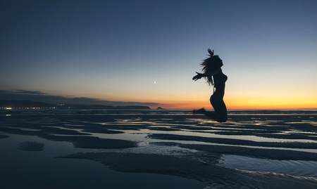 Young woman jumping by the sea at sunset LANG_EVOIMAGES