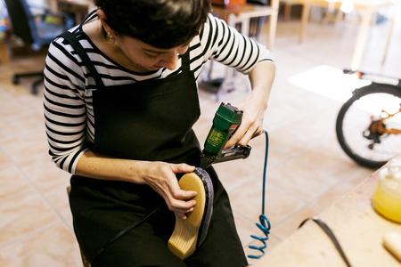 Clogmaker working in her workshop LANG_EVOIMAGES
