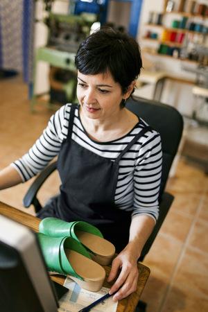Shoemaker using computer in her workshop LANG_EVOIMAGES