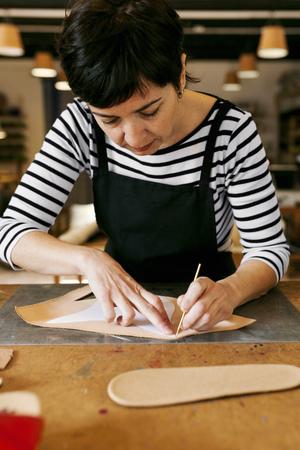 Shoemaker working on template in her workshop LANG_EVOIMAGES