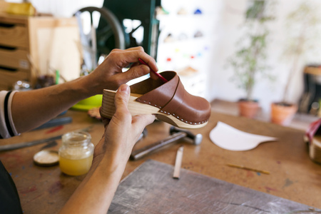 Close-up of clogmaker working in her workshop