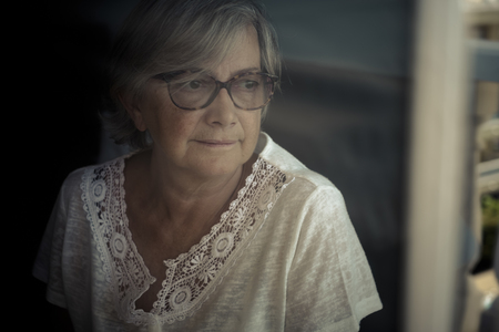 Portrait of senior woman looking through window LANG_EVOIMAGES
