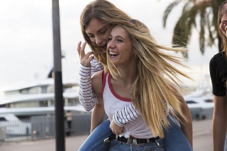 Laughing young woman giving her friend a piggyback ride LANG_EVOIMAGES