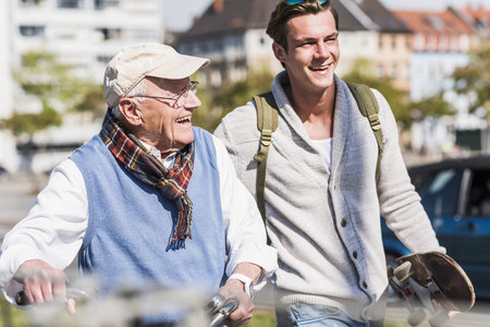 Happy senior man with adult grandson in the city on the move LANG_EVOIMAGES