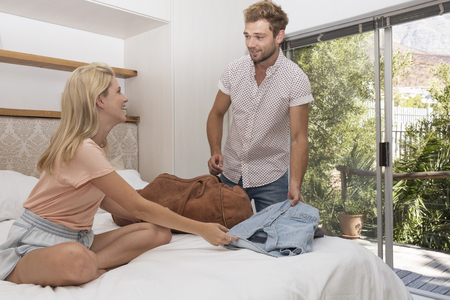 Young couple packing bag in bedroom