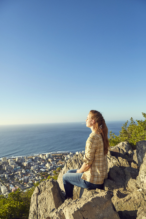 South Africa, Cape Town, Signal Hill, young woman sitting on rock with view to the city and the sea