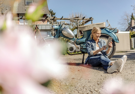 Smiling woman sitting at vintage motorcycle using tablet