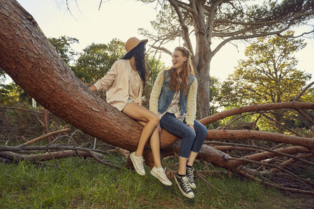 Two young women sitting and talking on tree trunk LANG_EVOIMAGES