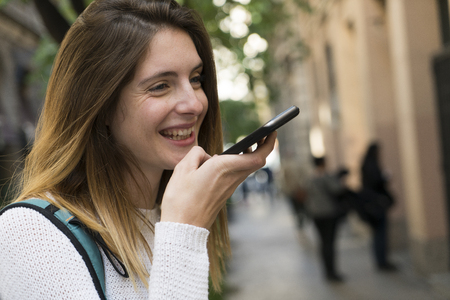 Happy young woman using cell phone in the city LANG_EVOIMAGES
