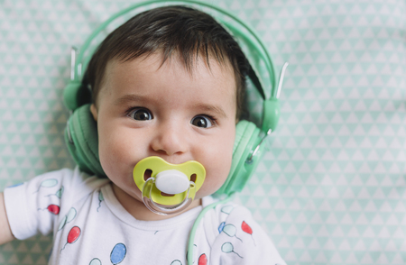 Portrait of baby girl with headphones and pacifier LANG_EVOIMAGES