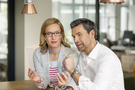 Businessman and woman using futuristic portable device