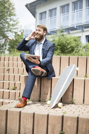 Businessman with skateboard, tablet and earphones on the phone LANG_EVOIMAGES