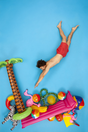 Man having fun on his vacation, jumping into the water LANG_EVOIMAGES