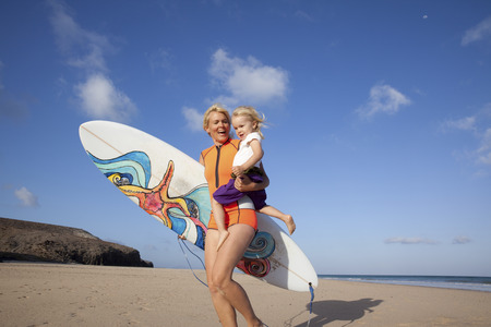 Spain, Fuerteventura, happy mother and daughter walking with surfboard on the beach LANG_EVOIMAGES