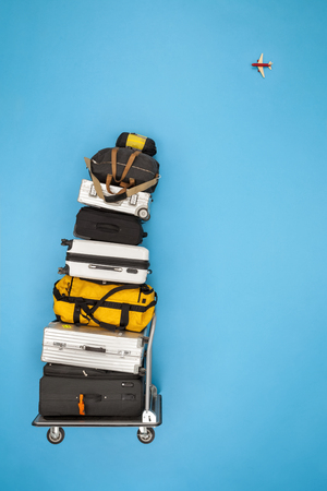 Stacked luggage and plane flying in the sky LANG_EVOIMAGES