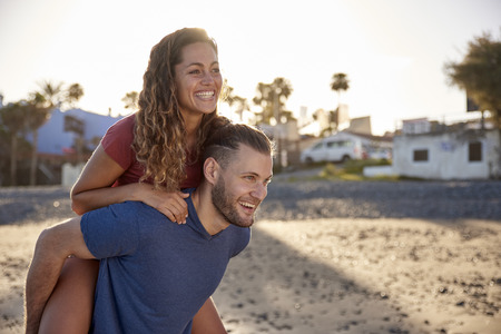 Young man giving his girlfriend a piggyback ride on the beach LANG_EVOIMAGES