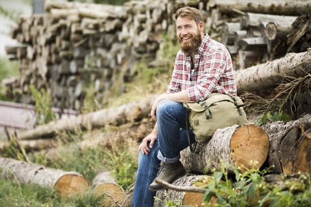 Laughing bearded man sitting on stack of wood LANG_EVOIMAGES