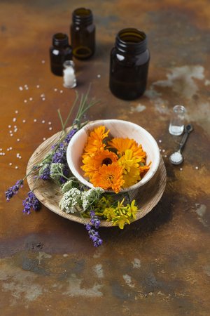 Blossoms of medical plants, medicine flasks and globules on rusty ground LANG_EVOIMAGES