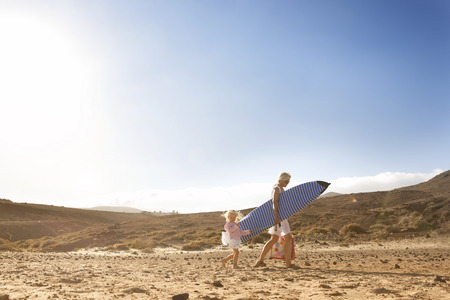 Spain, Fuerteventura, mother and daughter walking with surfboard on the beach
