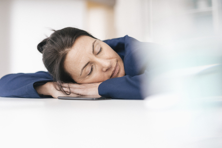 Overworked woman sleeping on desk in office LANG_EVOIMAGES