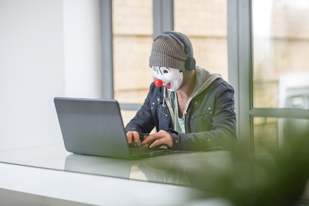 Employee wearing mask and working on laptop LANG_EVOIMAGES