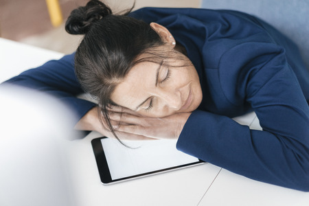 Overworked woman sleeping on tablet in office LANG_EVOIMAGES