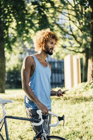 Young man with bicycle and cell phone in park