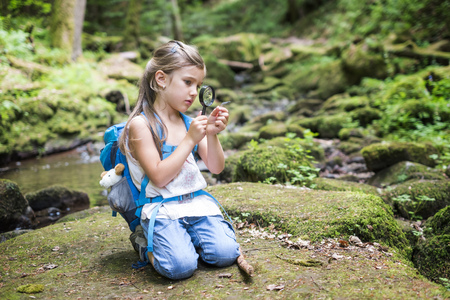 Little girl with magnifier crouching on rock in the woods watching a feather LANG_EVOIMAGES