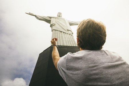 Brazil, Rio de Janeiro, Corcovado, Man praying at Jesus Christ the Redeemer statue LANG_EVOIMAGES