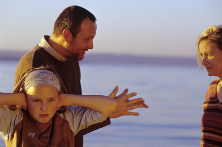 Parents in argument, girl (10-11) covering ears at beach LANG_EVOIMAGES