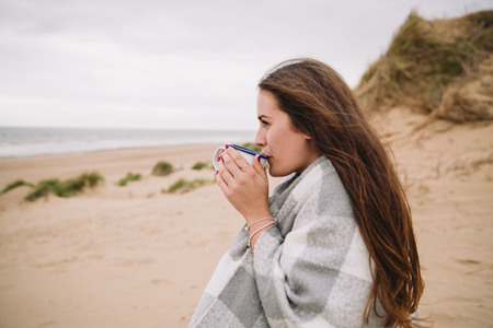 Young woman with cup of hot chocolate on the beach LANG_EVOIMAGES