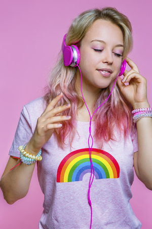 Portrait of young woman listening to music with headphones in front of pink background LANG_EVOIMAGES