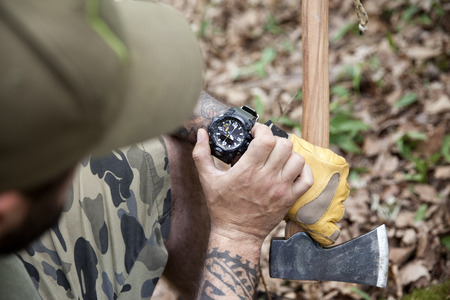 Close-up of man with axe in forest checking the time