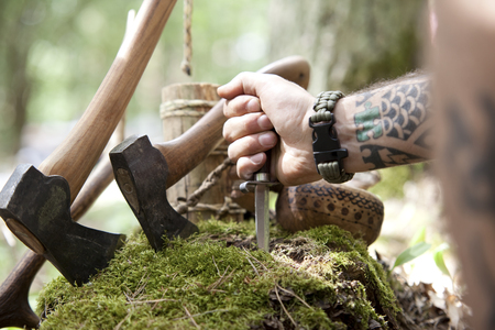 Axes, tree stump and hand holding knife in the forest LANG_EVOIMAGES