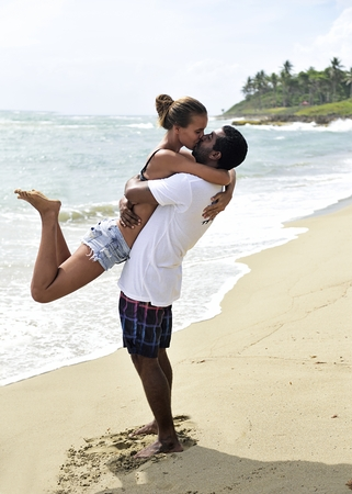 Happy couple kissing on the beach LANG_EVOIMAGES