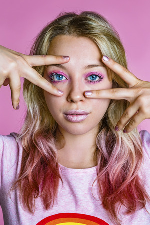 Portrait of rouged young woman with dyed hair in front of pink background LANG_EVOIMAGES