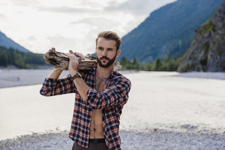 Germany, Bavaria, portrait of young man carrying firewood on his shoulder in nature