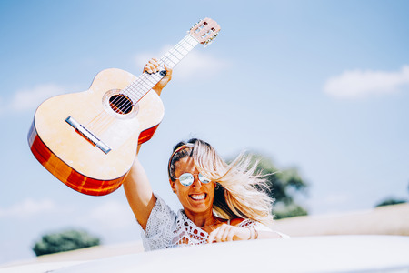Happy young woman holding her guitar aloft, standing in her van on a road trip LANG_EVOIMAGES