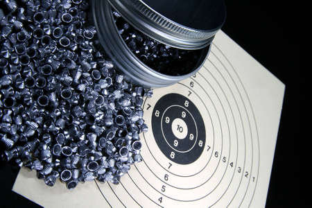 bb gun: Pellets and target against black background
